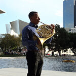 Malik Taylor plays the french horn in a plaza in downtown LA