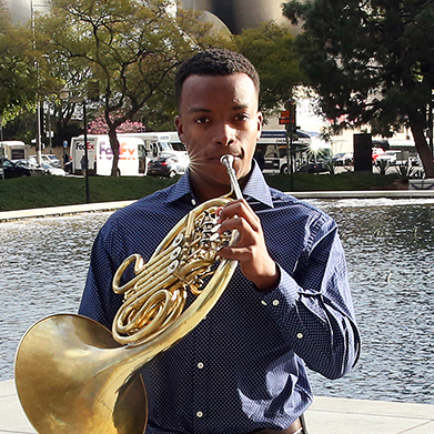 A musician plays the french horn and looks into the camera
