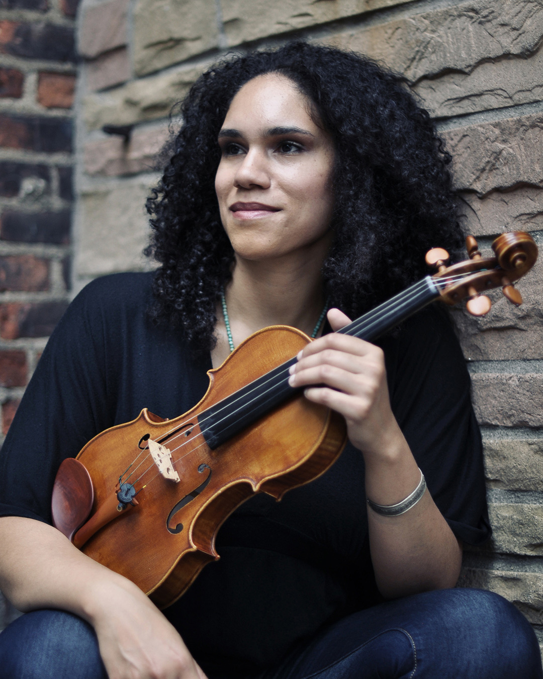 portrait of Jessie Montgomery holding a violin beside a brick wall