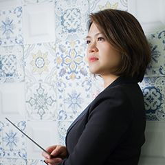 Julia Tai in formal attire holding conducting baton