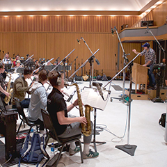 Musicians in a recording studio following a conductor