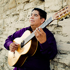 Tony Ybarra pictured holding a guitar beside a stone wall