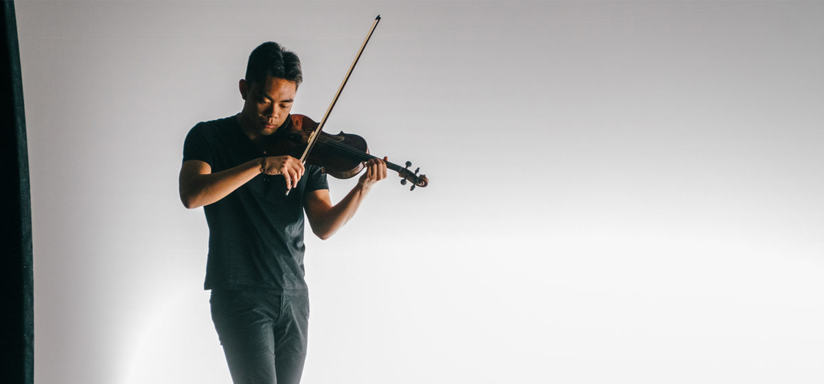 Violinist dressed in black, performing on a sharply lit stage