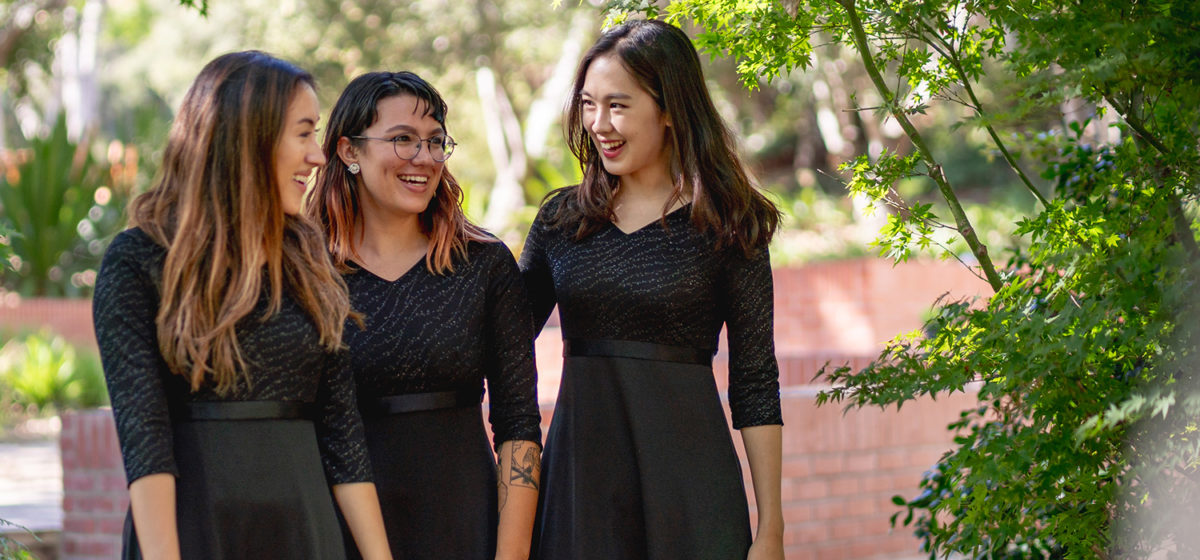 Three students in formal dress walking through a garden