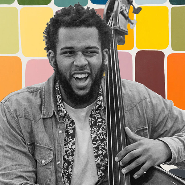 A black and white image of a double bassist playing with a colorful background