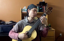 Robert Wang wears a bandana and plays a classical guitar in a dorm room