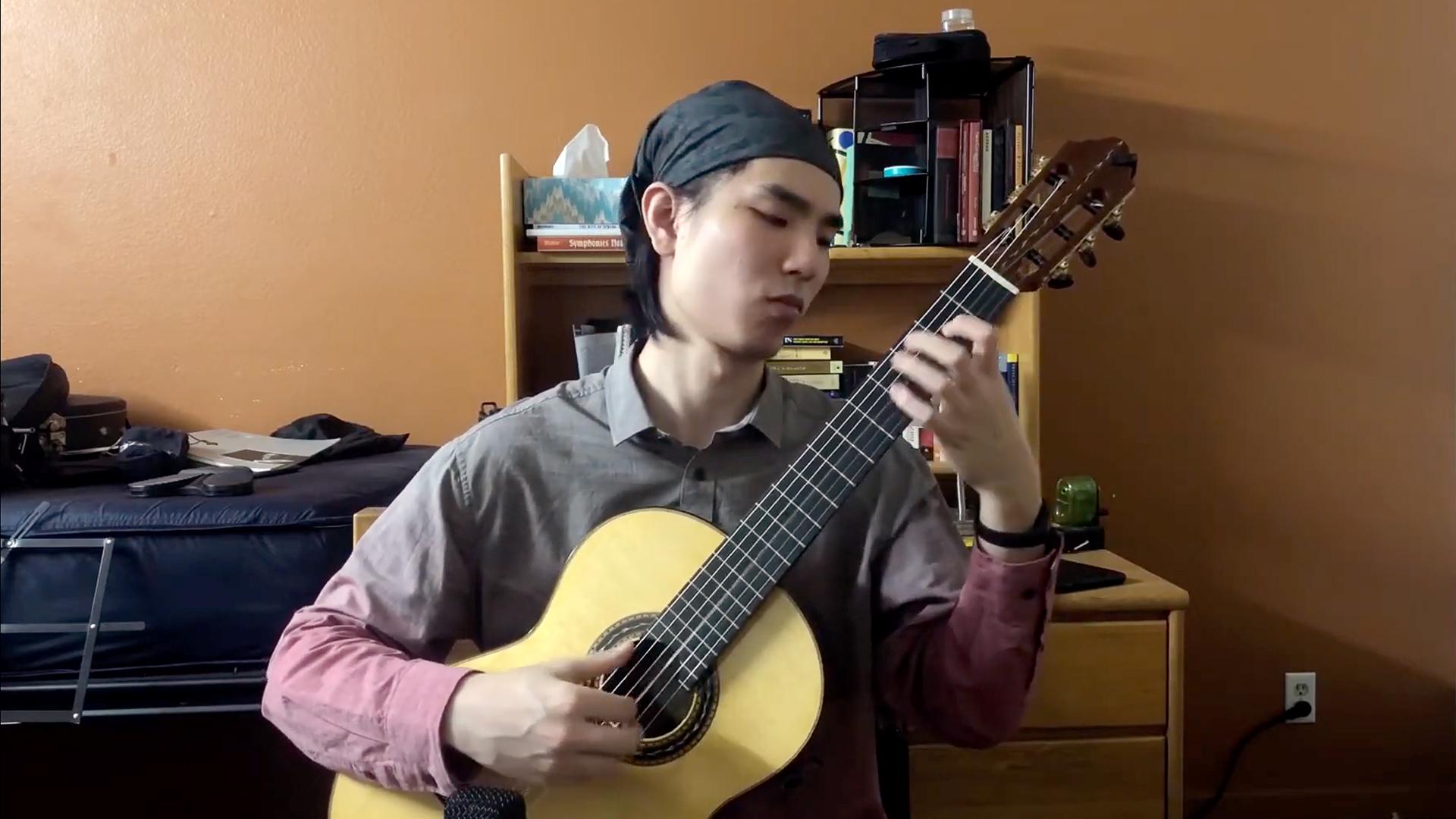 Robert Wang wears a bandana and plays a classical guitar in a dorm room