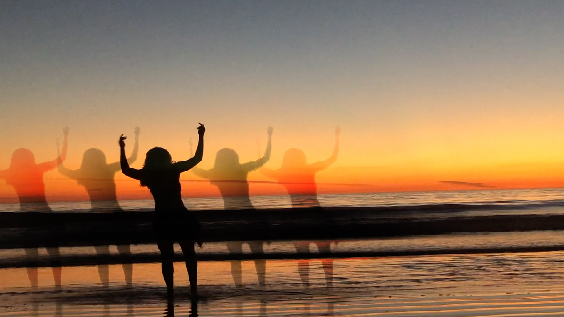 A dancer holds their hands above their head, standing on a beach at sunset.