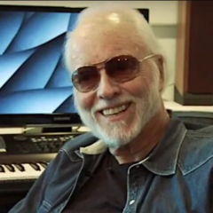 Perry Botkin Jr. wearing sunglasses and sitting beside a piano keyboard