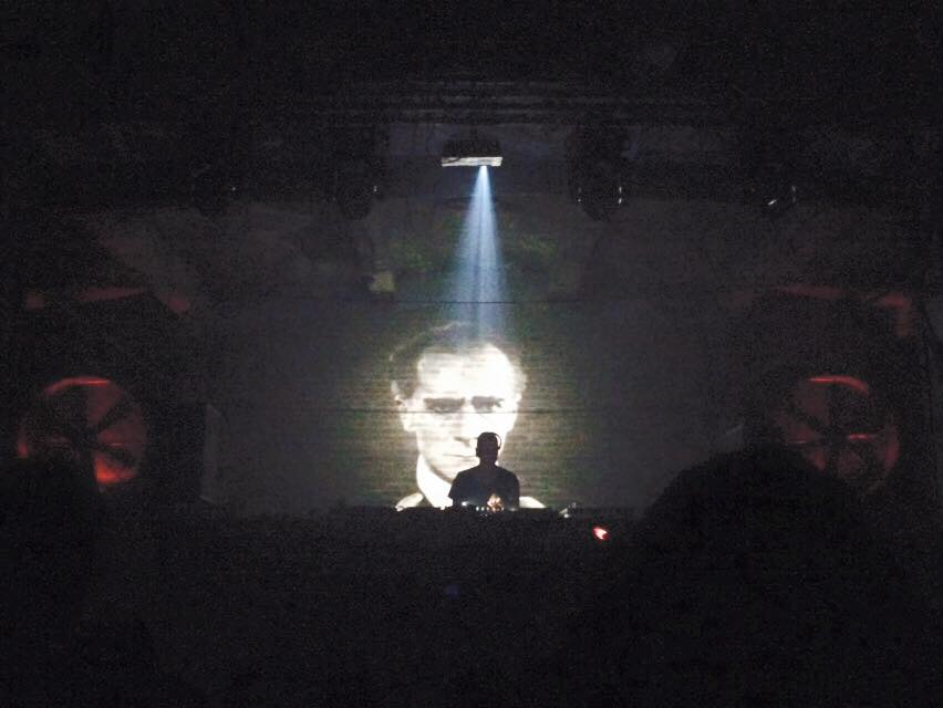 Music DJ performs in a dark indoor club with video projection