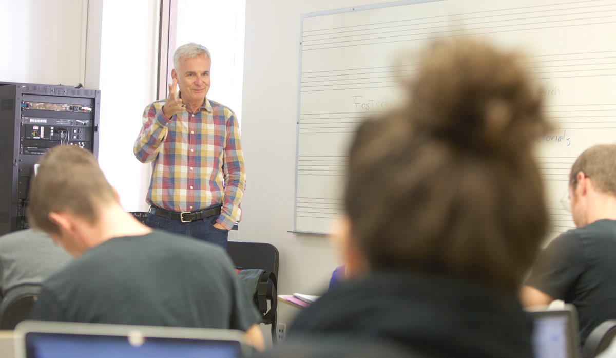 Ken Foster teaches in a classroom for a group of students