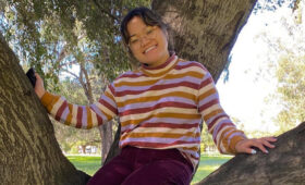Smiling student sitting in a tree.