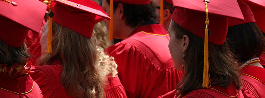 Outdoor photo of graduates wearing red caps and gowns