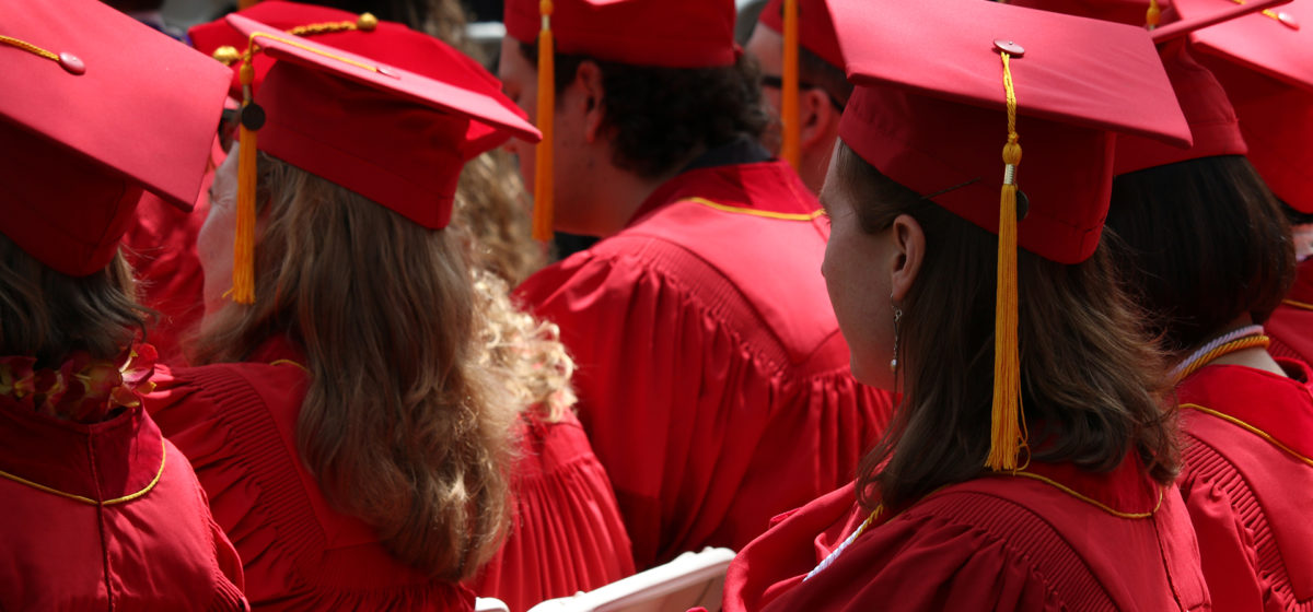 Outdoor photo of graduating class wearing red caps and gowns