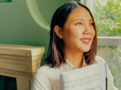 Smiling student holding sheet music