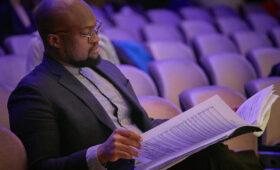 Vimbayi Kaziboni reads sheet music in an auditorium
