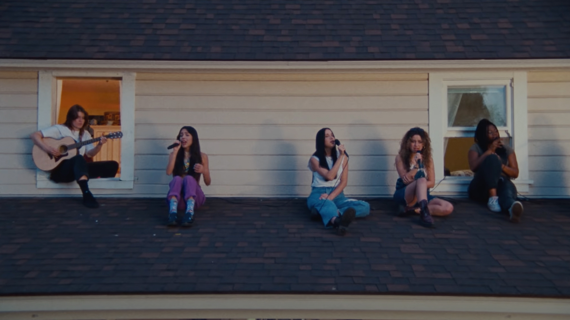 Photo of singers and guitarist performing on the roof of a house
