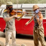 Photo of violinists playing outside, wearing masks