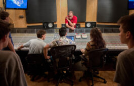 Students gather around a studio mixing board