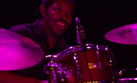 Popular Music drummer performing onstage with purple light
