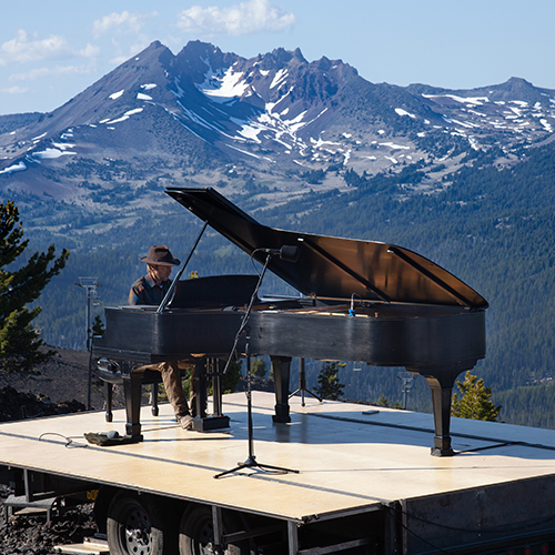 Hunter Noack performs outdoors on a Steinway grand piano in front of a mountain