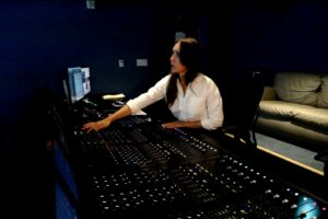 Photo of Danielle Dupre in front of a mixing board at Skywalker Sound.