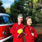 Photo of two violinists posing outside their VW bus